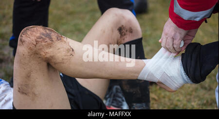 Soccer, football concept. Injured footballer lay down on field. Physiotherapist puts bandage on his ankle. Blurred background, close up view. - Stock Photo