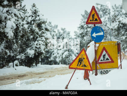 Under construction signs in snow. Warning symbols about street reconstruction. Snowy road and forest background. - Stock Photo
