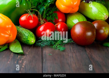 green and red color vegetables,  tomatoes, cucumber, peppers, fragrant herbs on an old wooden table, Top view, copy space - Stock Photo