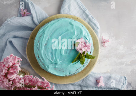 Blue stylish cake with flowers and mint. Copy space, top view. - Stock Photo