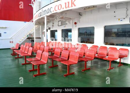 Bright  red seats on the passenger deck  of the CalMac ferry from Wemyss Bay to Rothesay - Stock Photo