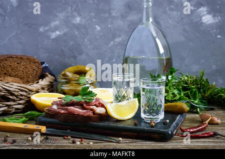 Two shot glasses of vodka with lemon slice, pickled cucumbers and rye bread with salted bacon on the dark background. Traditional strong drink and app - Stock Photo