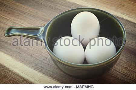 Three white eggs in a dark green ramekin bowl set on a textured wood cuttingboard - Stock Photo