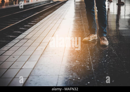 Feet of a young man wearing jeans who is waiting for the train at the platform of the train station. - Stock Photo