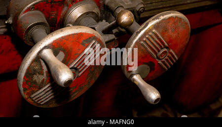 Vintage antique automotive machine shop red worn adjustment wheels with handles - Stock Photo