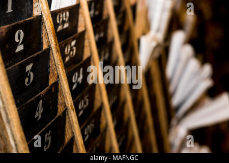 Numbered old and faded time clock punch card wall rack with papers in the distance - Stock Photo