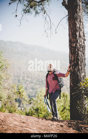 12546d41e452 ... Hiker with map and big traveling backpack traveling to the mountain. -  Stock Photo
