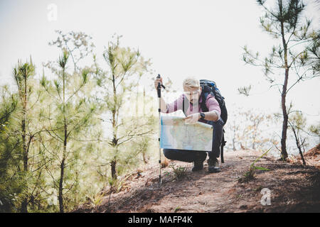 d576a3623a4e Hiker with map and big traveling backpack traveling to the mountain. -  Stock Photo