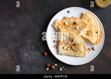 Crepes Suzette with honey and nuts on white plate over dark background, copy space. Delicious homemade Crepes for breakfast. - Stock Photo