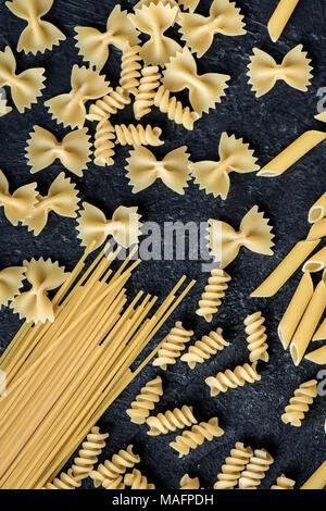 Assorted uncooked raw pasta on black background. Italian pasta: penne, farfalle, spaghetti, fusilli. - Stock Photo