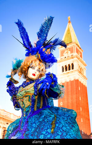 Venice, Italy - 9th February 2018: Carnival of Venice, beautiful woman mask at Piazza San Marco with Campanile. - Stock Photo