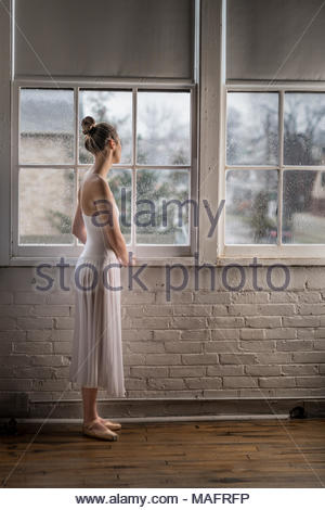 Ballerina Stretching on a wood floor with a brick wall in the background. - Stock Photo