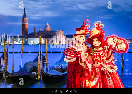 Venice, Italy - 11th February 2018: Carnival of Venice, beautiful mask at Mark's Square with St. George island in the background. - Stock Photo