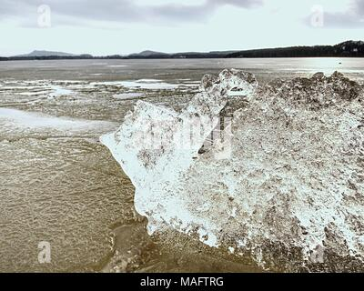Ice melting on sandy beach.  Detail of ice floe with deep cracks inside. The end of crue winter coming. - Stock Photo