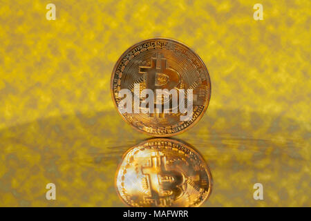 Golden Bitcoin Crypto Currency on a  Yellow. - Stock Photo