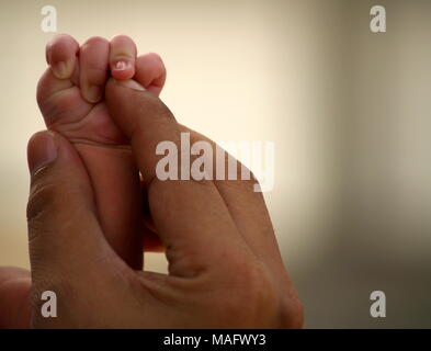Newborn Baby Holding Father Hand - Stock Photo