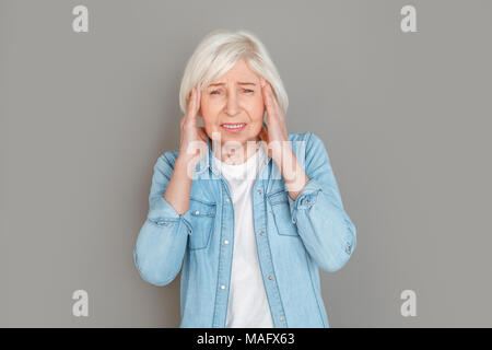 Aged female wearing jeans jacket studio isolated on grey background looking camera suffering from pain headache holding head - Stock Photo