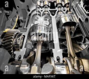 Inside view of modern engine, close up detail of two pistons in cylinder with four valves,some gears aside. - Stock Photo
