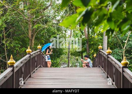 Young Asian man photographs a smiling young Asian woman with blue umbrella on wooden bridge in park in Bang Krachao (Bang Kachao), Bangkok, Thailand. - Stock Photo