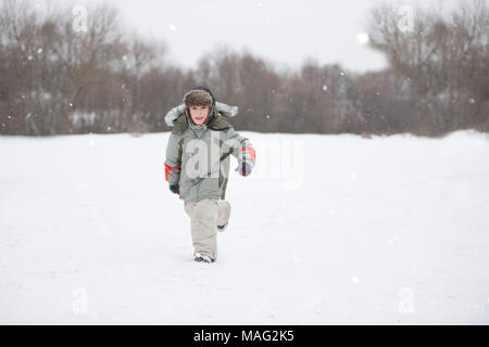 A little boy runs through the snow in warm clothes and a hat with a fur hat.Child on a winter day - Stock Photo