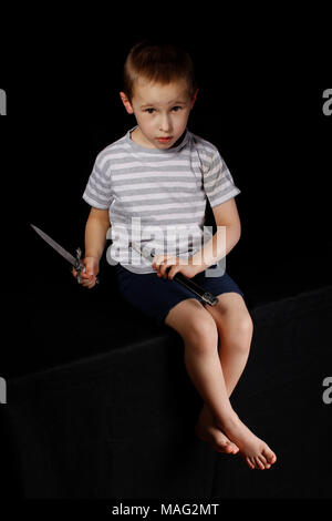 Little boy with a dagger on a black background - Stock Photo