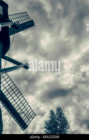 beautiful photo shot of a Dutch windmill against a cloudy background with a tree at the bottom of the photo - Stock Photo