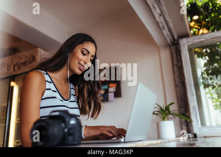 Woman blogger using laptop at home wearing earphones. Woman sitting with a professional camera on the table working on her laptop computer. - Stock Photo