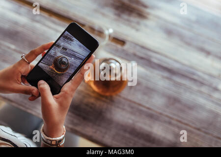 Close up of a woman capturing photos of a glass teapot using a mobile phone for her food blog. Food blogger shooting photos for her blog. - Stock Photo