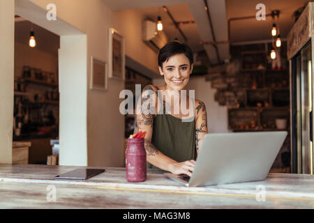Woman entrepreneur working on laptop computer at home with a smoothie on the table. Woman enjoying a glass of smoothie while working at home. - Stock Photo