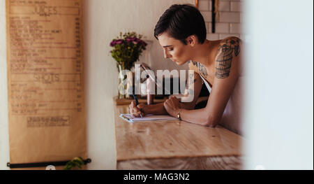 Woman standing at the counter of her cafe noting orders. Restaurant owner making notes standing at the billing counter.