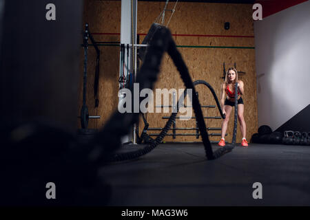 Portrait of sports woman in training with two ropes - Stock Photo
