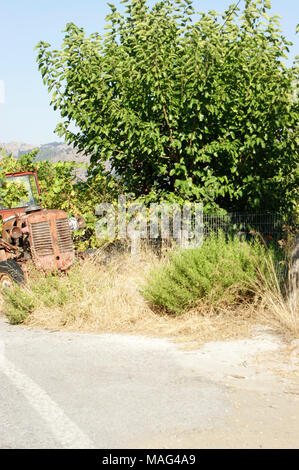 Old and rusty tractor on the farm, agriculture in Greece in Crete - Stock Photo