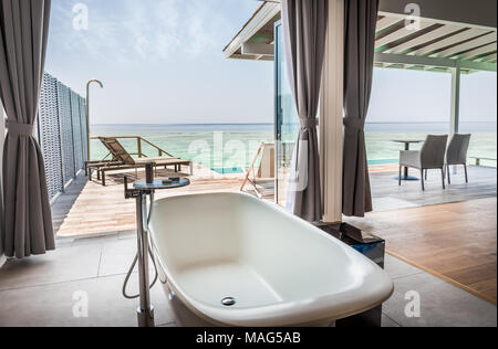 Interior of luxurious water villa bathroom with amazing view in Maldives - Stock Photo