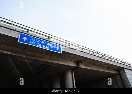 Courage Ahead Blue Road Sign Against Clear Sky - Stock Photo