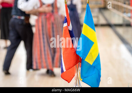 Scandinavian and Swedish flags stand center while dancers perform a traditional Scandinavian dance in the background - Stock Photo