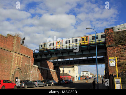 On a sunny spring day a Mersey rail electric train crosses a high bridge over the road as it leaves Sandhills station in Liverpool. - Stock Photo