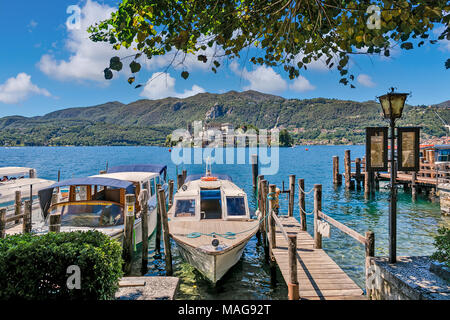 Boats anchored along small wooden pier on Lake Orta - famous and very popular tourist resort and travel destination in Northern Italy. - Stock Photo