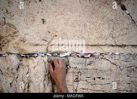 Jerusalem, Israel. 02nd Apr, 2018. JERUSALEM, ISRAEL - APRIL 2, 2018: A hand reaching out to paper notes containing written prayers to God placed into the cracks of the Western Wall during the Jewish feast of Passover. Sergey Orlov/TASS Credit: ITAR-TASS News Agency/Alamy Live News - Stock Photo