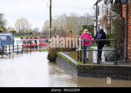 Tewkesbury, Gloucestershire - Bank Holiday Monday 2nd April 2018 - UK Weather: Visitors enjoy a walk alongside the  flooding at the confluence of the River Severn and the River Avon in Tewkesbury - further heavy rain is forecast  as local river levels rise. Photo Steven May  / Alamy Live News - Stock Photo