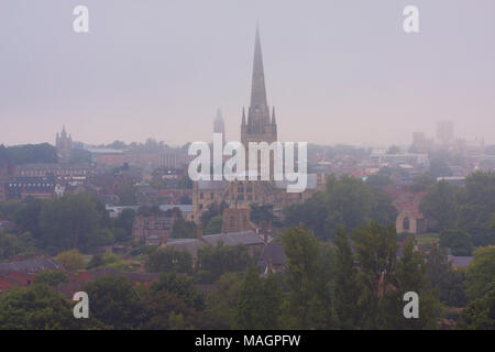 view of Norwich skyline with cathedral in distance on misty morning, East Anglia, England - Stock Photo