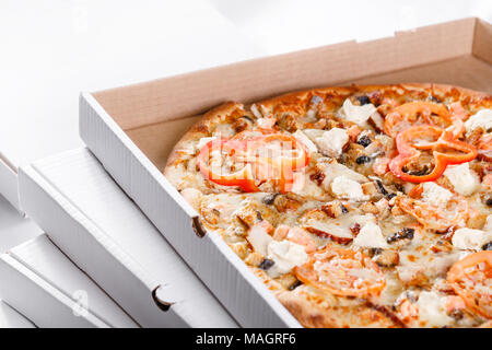 Pizza box delivery concept. Open box with hot tasty italian sliced pizza with salmon, eel, seafood, olives, basil, tomato, mushrooms. - Stock Photo