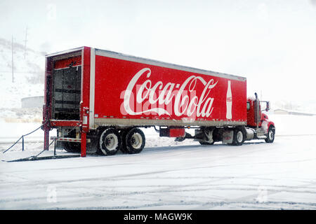 A red coca-cola truck unloading pop at a gas station in the snow. - Stock Photo