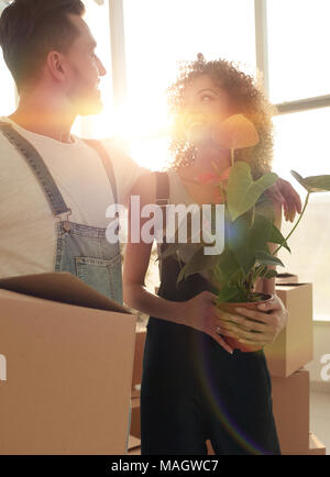 Close-up of a beautiful young couple is carrying things into a n - Stock Photo