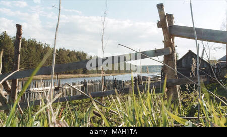Wooden fence and green grass with sun reflection and lake with blue sky background. Video. View of a farm gate leading into countryside. Countryside landscape - Stock Photo
