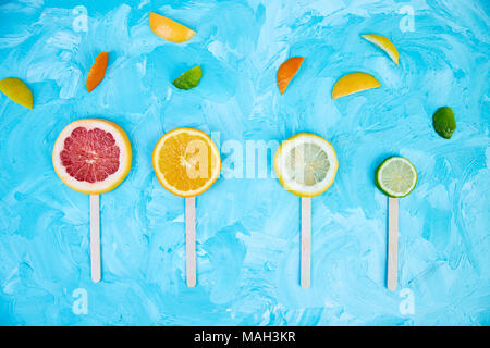 Citrus slice popsicles on a blue background. Flat lay. - Stock Photo