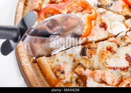 Italian kitchen and cooking concept - cook with cutter cutting pizza to pieces at pizzeria. Hot tasty sliced with salmon, eel, seafood, tomato. - Stock Photo