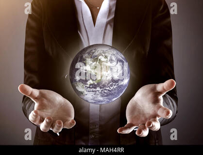 close up.businessman holding the globe.photo on a gray background - Stock Photo