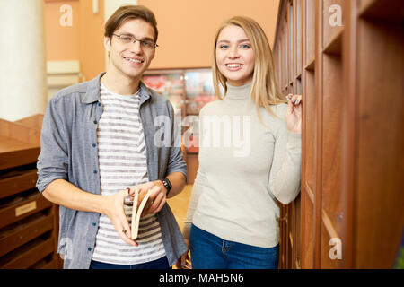 Positive couple of students choosing books in library - Stock Photo