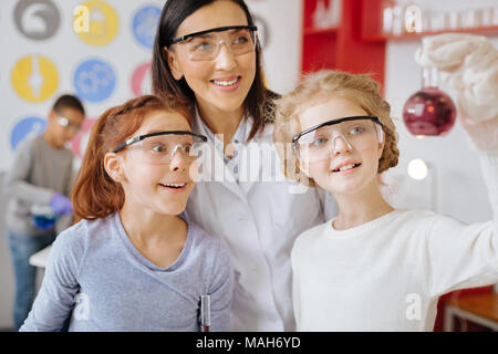 Cheerful students and teacher checking for sediment in flask - Stock Photo