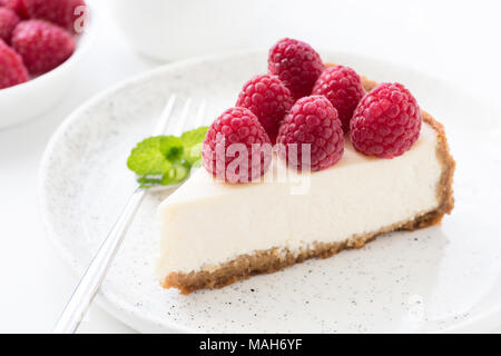 Cheesecake with fresh raspberries on white plate. Closeup view, selective focus - Stock Photo